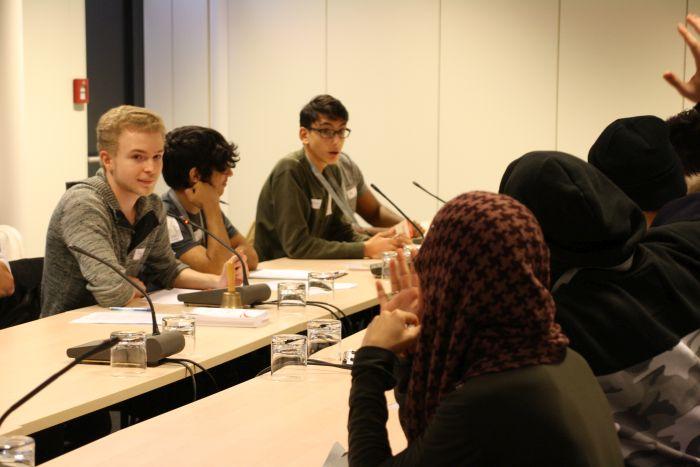 Lehrlinge sitzen um einen Tisch und stimmen ab