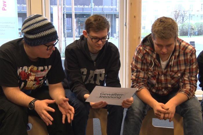 Lehrlinge sitzen auf Hockern