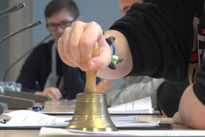 Lehrling hält Glocke im Ausschuss