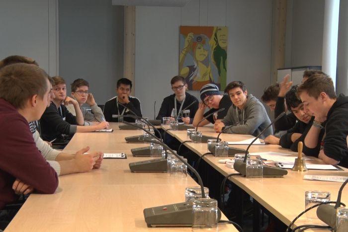 Lehrlinge sitzen am Tisch in einem Ausschusslokal