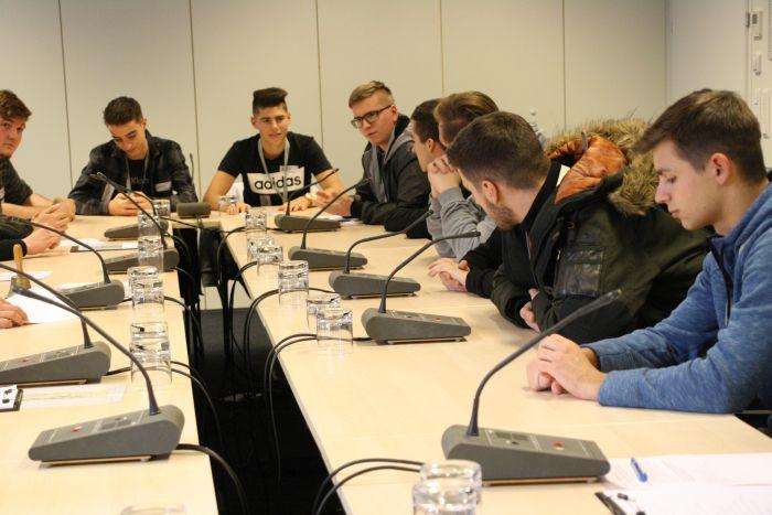 Lehrlinge sitzen an einem Tisch in einem Ausschusslokal