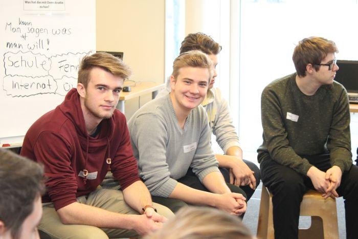 Drei Lehrlinge sitzen auf Hocker und lächeln in die Kamera