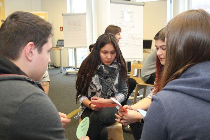 Vier Lehrlinge sitzen auf Hocker und halten Moderationskarten