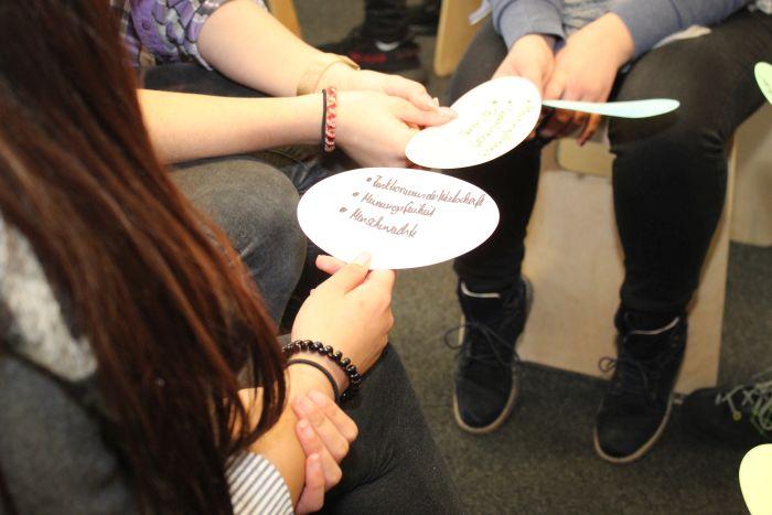 Lehrlinge sitzen auf Hocker und halten Moderationskarten