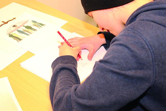 Lehrling sitzt am Tisch und zeichnet