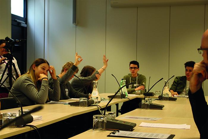 Lehrlinge sitzen am Tisch in einem Ausschusslokal und stimmen ab