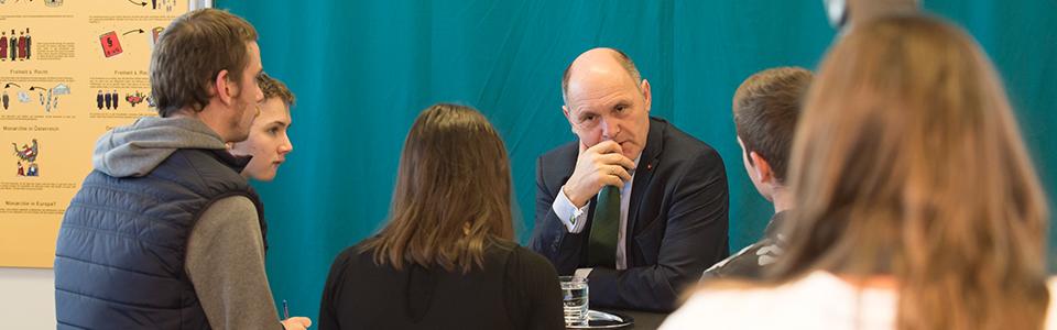 Lehrlinge sitzen im Kreis und diskutieren mit Politiker