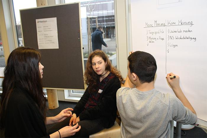 Lehrlinge sitzen auf Hockern und schreiben auf ein Plakat