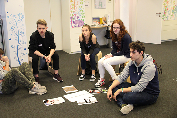 Lehrlinge sitzen auf Hocker bzw. am Boden und betrachten Bilder, die am Boden liegen