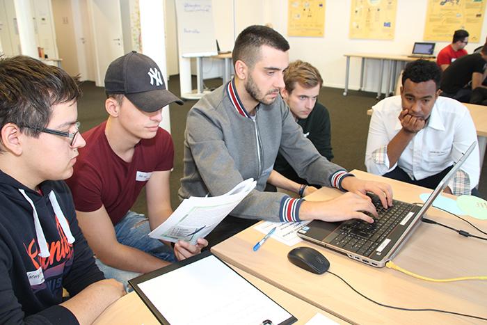 Lehrlinge sitzen vor Laptop und tippen