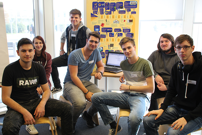 Sitzendes Gruppenbild von Lehrlingen vor Laptop