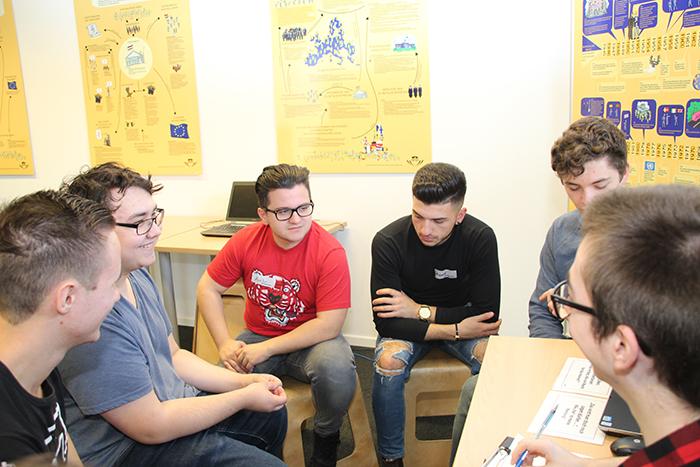 Lehrlinge sitzen im Halbkreis und diskutieren