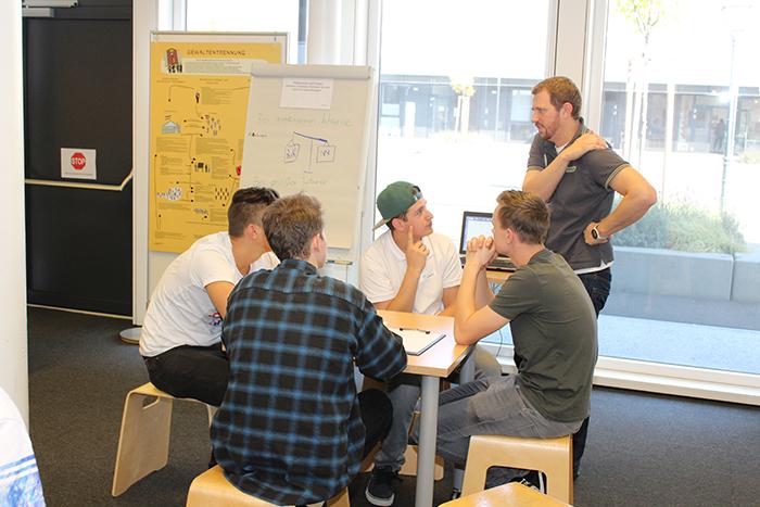 Lehrlinge sitzen am Tisch und arbeiten