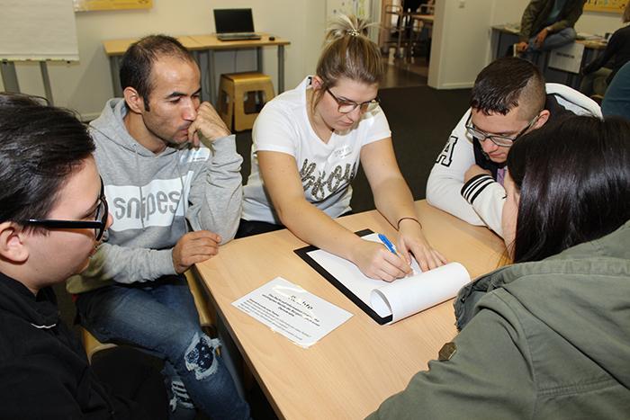 Lehrlinge sitzen um Tisch und diskutieren