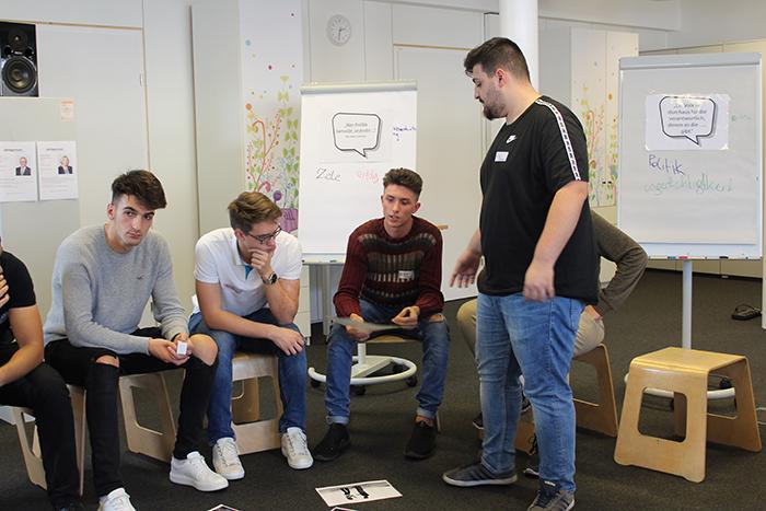 Lehrlinge sitzen auf Hocker und diskutieren