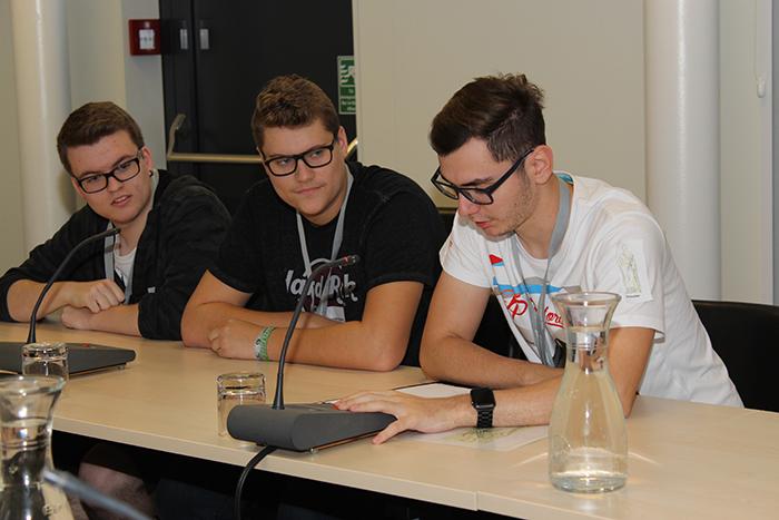 Lehrlinge diskutieren im Ausschuss und sprechen in ein Mikrofon
