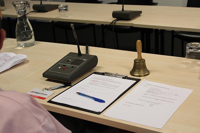 Mikrofon, Glocke und Schreibblock liegen am Tisch