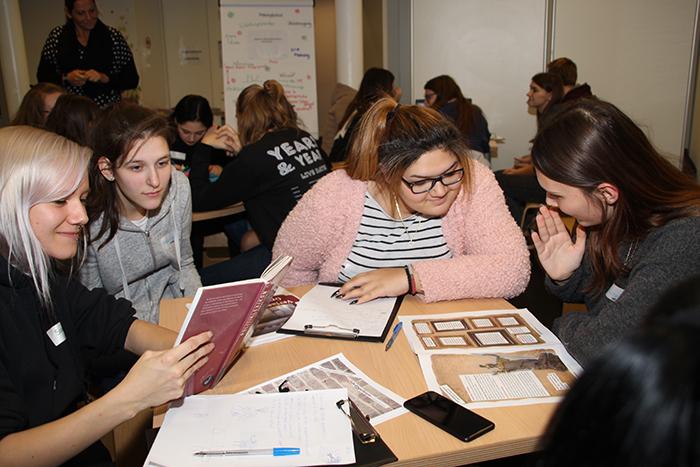 Lehrlinge sitzen am Tisch und lesen in Büchern