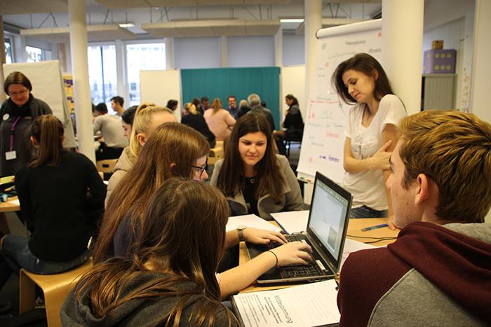 Lehrlinge sitzen am Tisch und arbeiten am Laptop