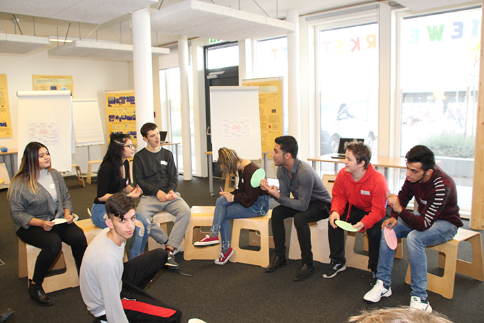 Lehrlinge sitzen im Sesselkreis und diskutieren