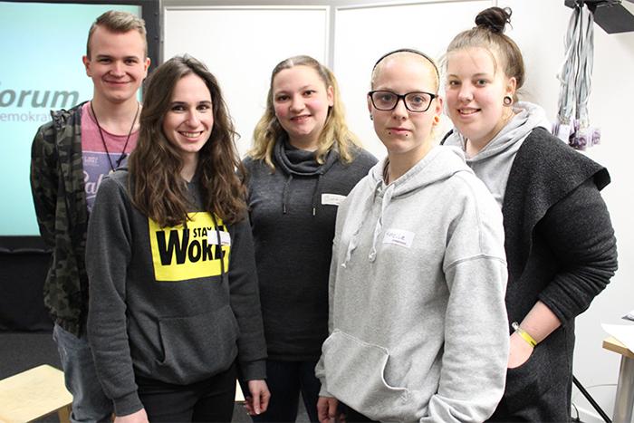 Lehrlinge stehen in einer Gruppe vor einer Leinwand