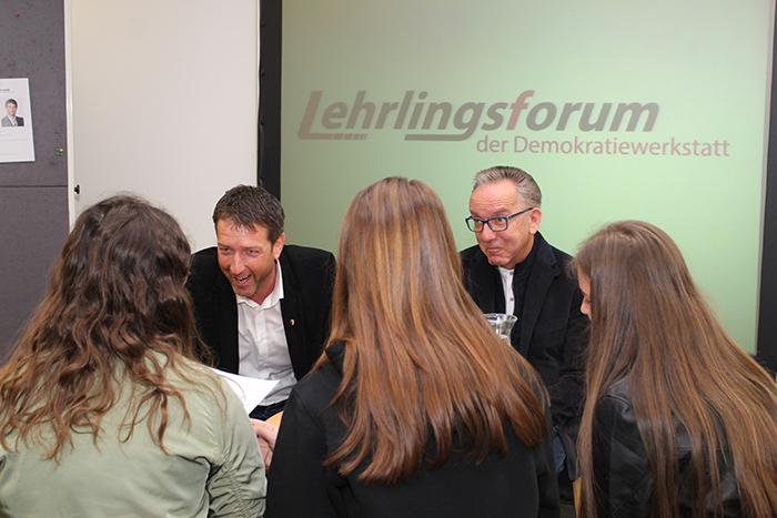 Lehrlinge sitzen im Sesselkreis und diskutieren mit Politiker