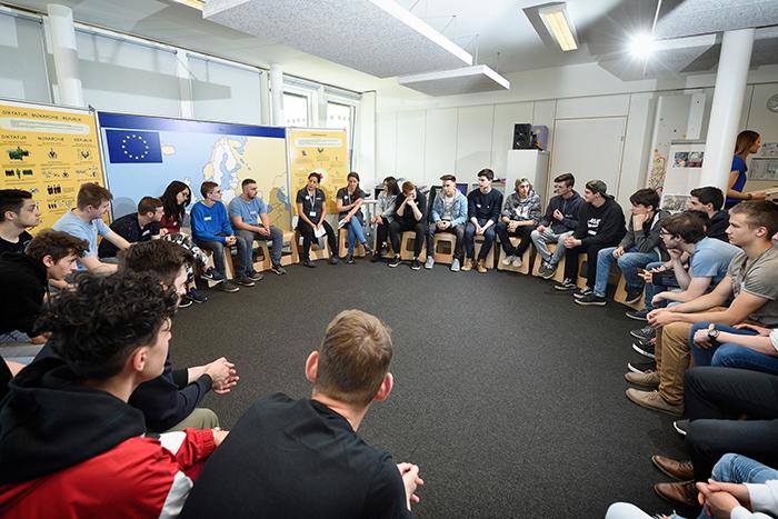 Lehrlinge sitzen im Sesselkreis