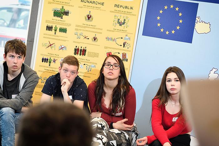 Lehrlinge bei der Gruppenarbeit vor einem EU-Plakat