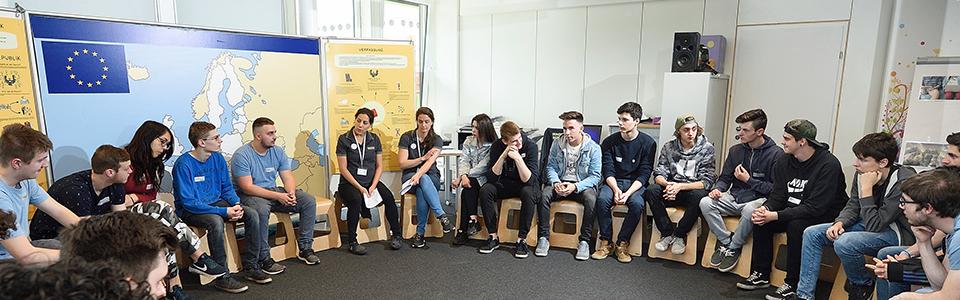 Lehrlinge sitzen im Kreis und diskutieren