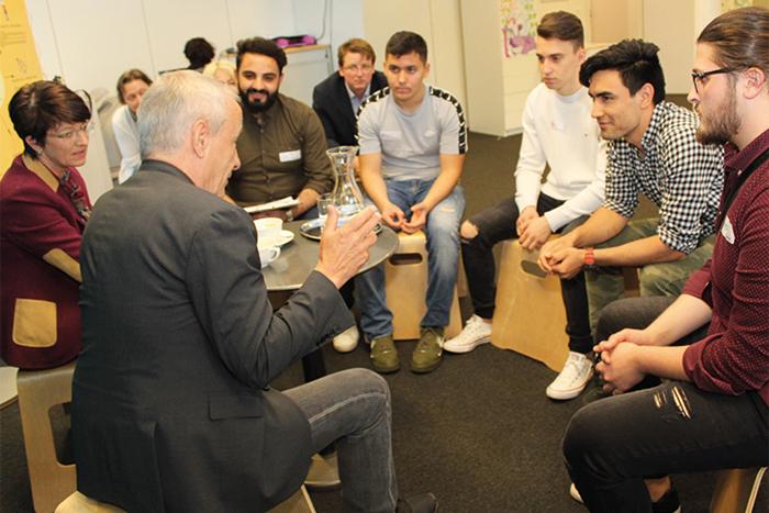 Lehrlinge sitzen im Sesselkreis und diskutieren mit PolitikerInnen