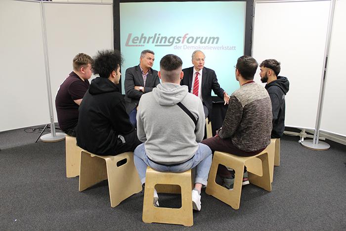 Lehrlinge sitzen im Sesselkreis und diskutieren mit Politikern