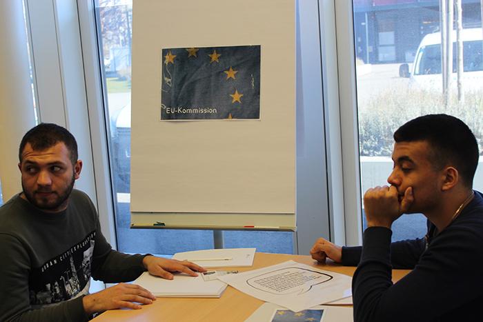 """Zwei Lehrlinge sitzen an einem Tisch, dahinter ein Plakat mit den Worten """"EU-Kommission"""""""