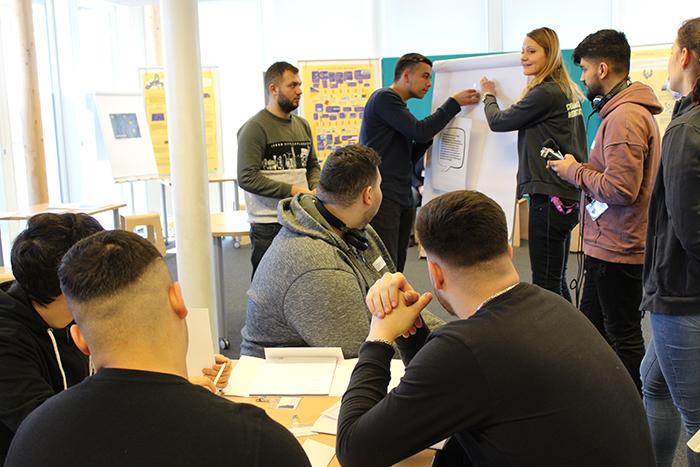 Lehrlinge sitzen bei einem Flipchart und kleben Zettel auf
