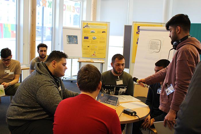 Lehrling interviewt mit Mikrofon andere Lehrlinge, die an einem runden Tisch sitzen