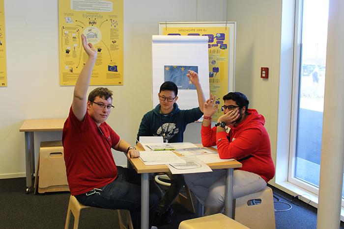 Drei Lehrlinge sitzen an einem Tisch und zeigen auf