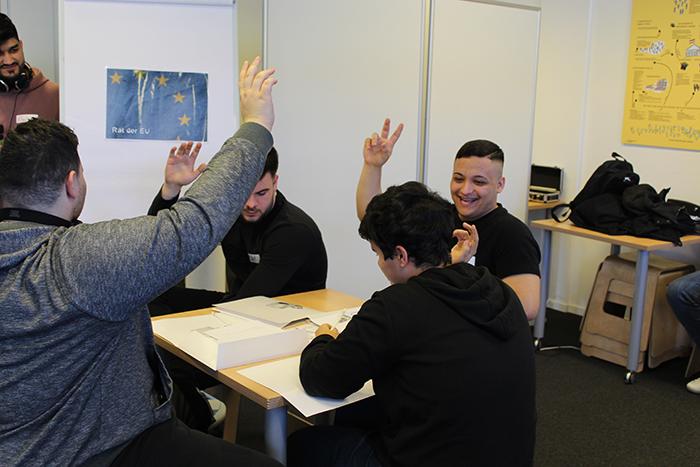 Vier Lehrlinge sitzen an einem Tisch und zeigen auf