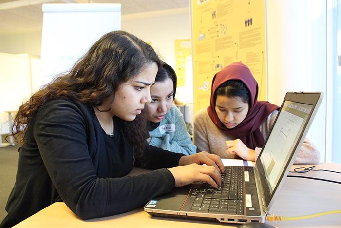 Drei Lehrlinge tippen in einen Laptop
