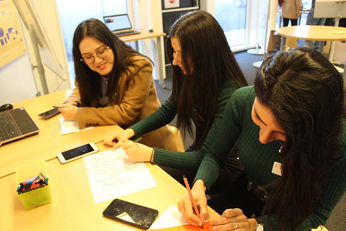 Lehrlinge sitzen an einem Tisch und beschreiben Kärtchen