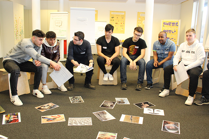 Lehrlinge sitzen auf Hocker im Halbkreis und betrachten Bilder, die am Boden liegen