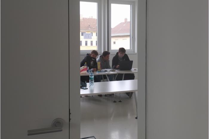 Durch einen Türspalt sind drei Lehrlinge am Tisch sitzend zu sehen
