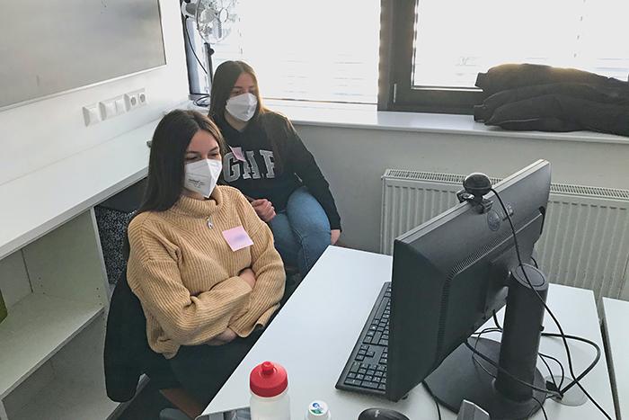 Zwei Lehrlinge sitzen an einem Tisch und arbeiten am Laptop