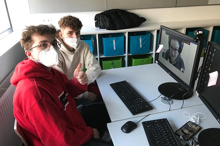 Zwei Lehrlinge sitzen an einem Tisch mit Laptop und zeigen ein Daumen-hoch