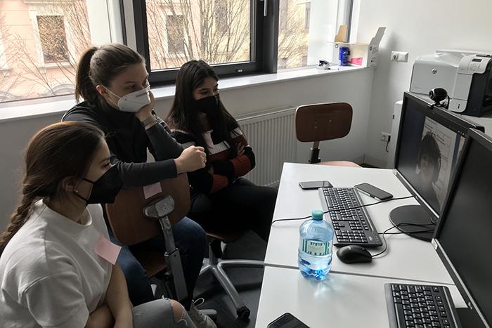 Drei Lehrlinge sitzen an einem Tisch und schauen in einen Laptop