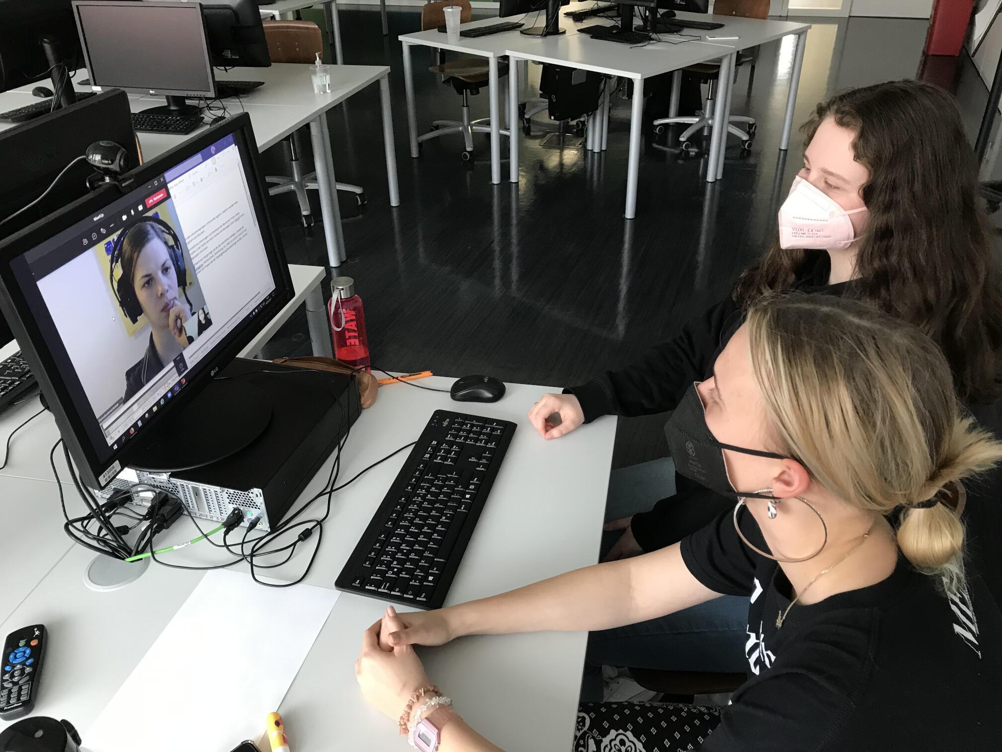 Zwei Lehrlinge sitzen an einem Tisch und schauen auf einen Computerbildschirm