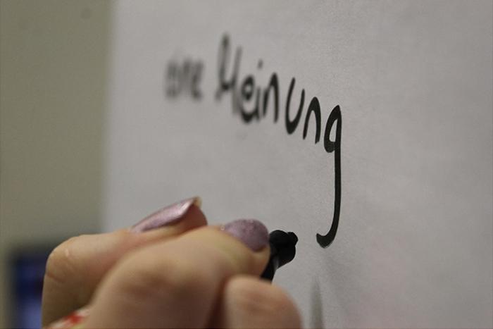 Hand beschriftet Flipchart mit dem Schriftzug eure Meinung