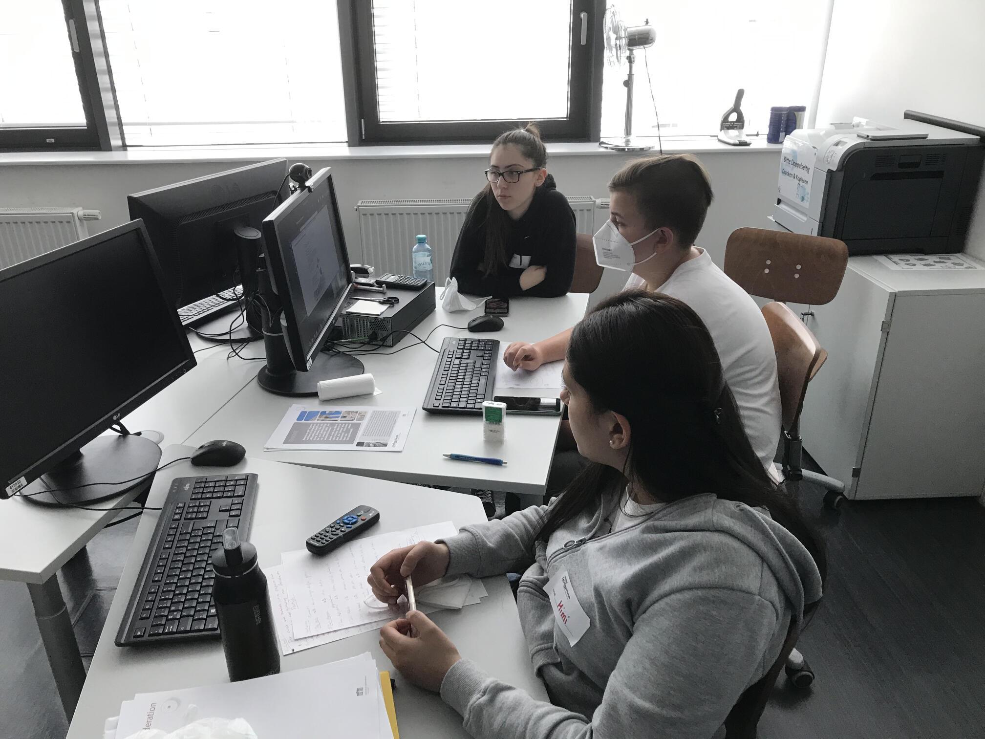 Drei Lehrlinge sitzen an einem Tisch und arbeiten am Computer
