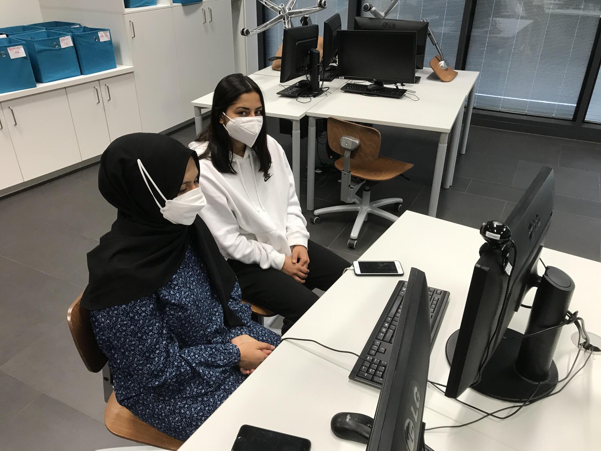 Zwei Lehrlinge sitzen an einem Tisch mit Computer