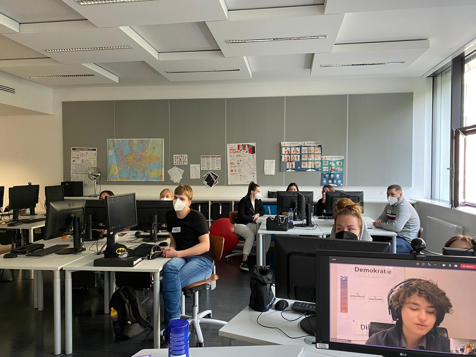 Lehrlinge sitzen im Klassenzimmer an Tischen mit Computer