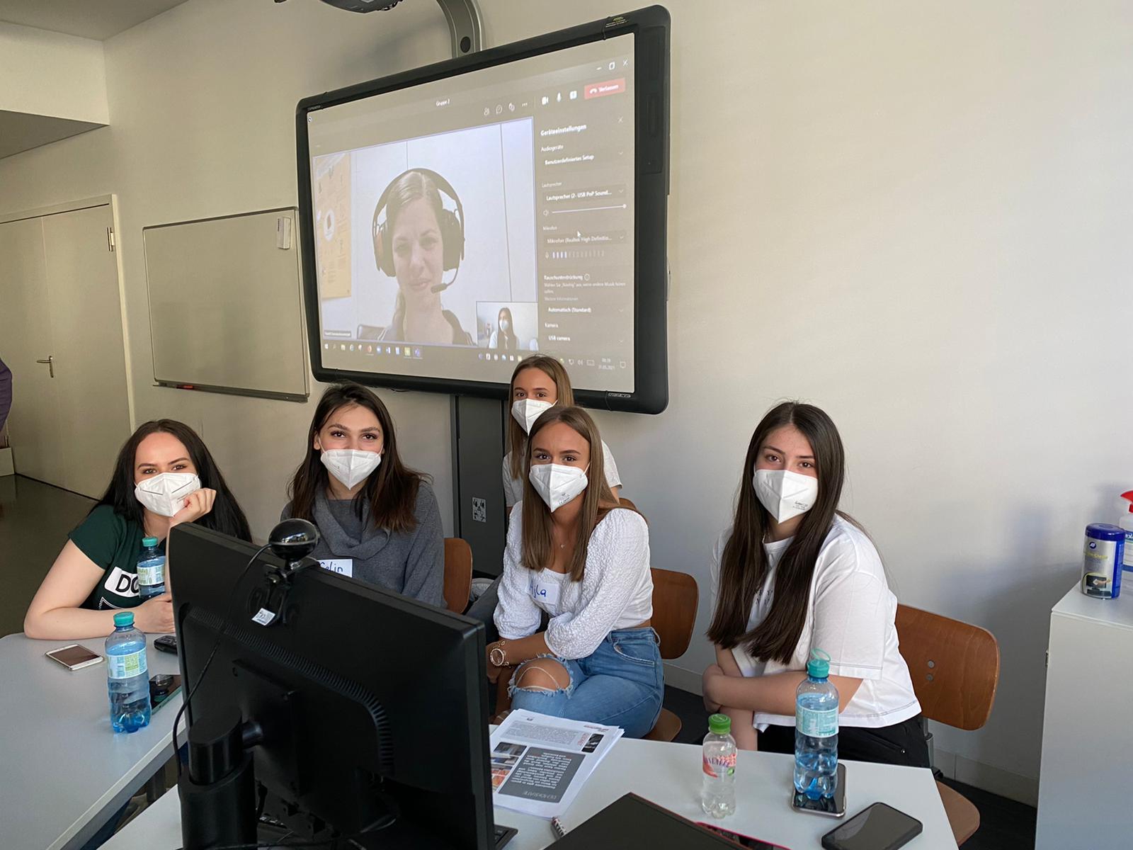Fünf Lehrlinge sitzen an einem Tisch mit Computer, im Hintergrund ist eine Leinwand zu sehen