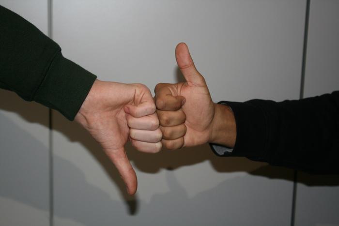 """Zwei Hände zeigen """"Daumen hoch"""" und """"Daumen runter"""""""